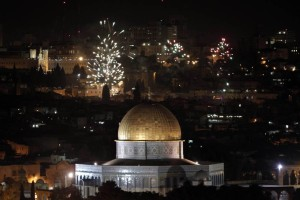The golden dome of the Dome of the Rock, Islam's third holiest place and part of the al-Aqsa Mosque complex, is seen as fireworks light the skies of Jerusalem to mark the new year on January 1, 2013. AFP PHOTO/AHMAD GHARABLI